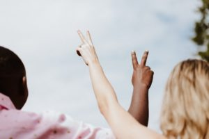 Two people, a black man and a white woman, holding their hands up in peace signs